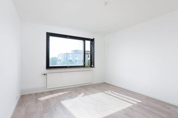 Valkoiseksi maalattu huone ikkunalla